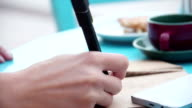 Hands of woman writing in notebook, cup of coffee, smartphone video