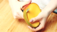 Hands Peeling Mango Over Cutting Board video