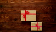 Hands placing some present boxes on a wooden flat lay video