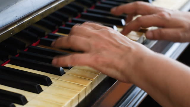 Hands playing on piano keyboard video