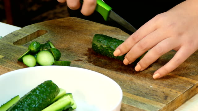 Hands prepare cucumber for salad video