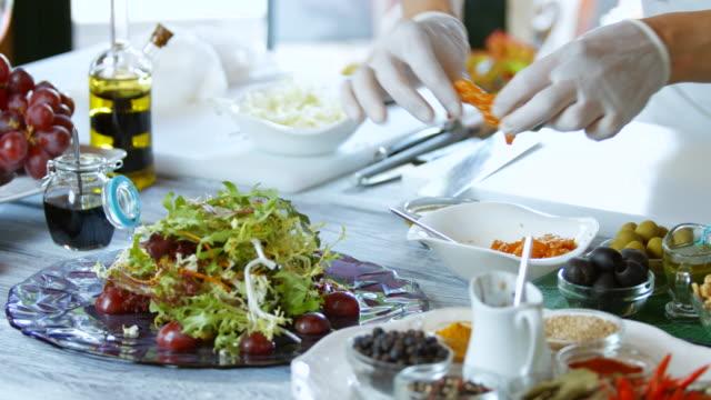 Hands put fish in salad. video