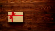 Hands putting a gift box on table and adding a greeting card in a form on heart video