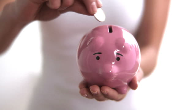 Hands putting coin into piggy bank video