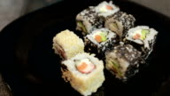 Hands putting sushi onto plate. Man prepares food at table. Time to serve the dish video