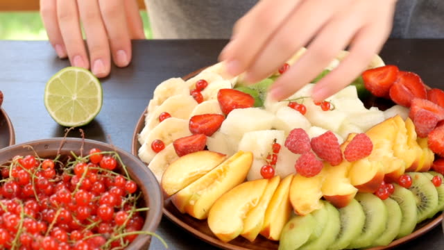 Hands serving fruit and berry plate . video