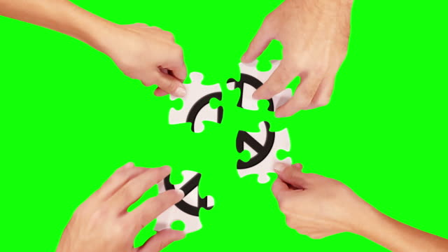 Hands solving a puzzle. Green Screen and Wood. Peace sign. video
