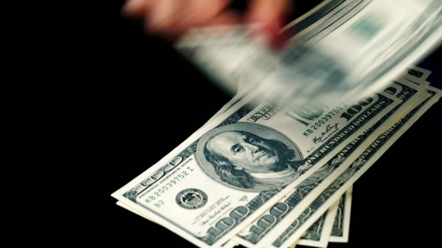 Hands spread banknotes of hundred dollars on the table video