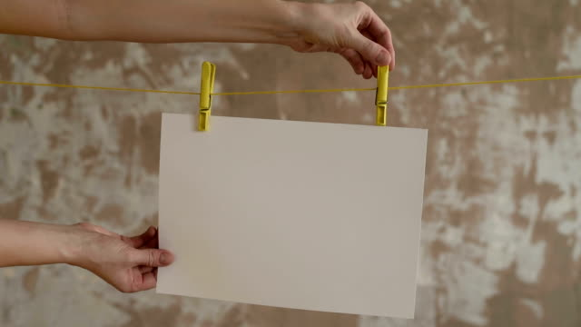 Hands taking a card off the pegs video