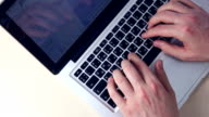 Hands typing on tablet financial information video