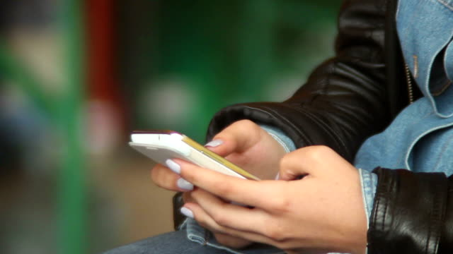 Hands typing sms messages touch phone, female fingers, public video