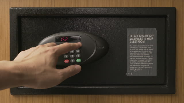 Hands unlocking combination to safe in the hotel room video