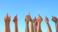 Hands up with thumbs-up against blue sky video