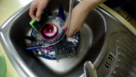 hands washing dishes under running water in kitchen sink. video