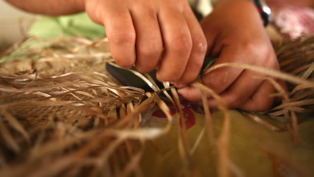 Hands weaving a fine mat video