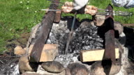 Hands with gloves put fish in foil into hot ember and meat on skewer baking in retro fireplace. FullHD video