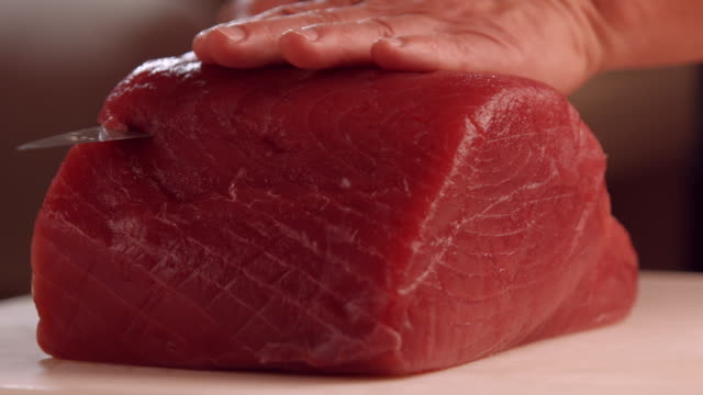 Hands with knife cutting meat. video