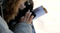 Hands with smartphones, pen and handouts, in black leather gloves, three people in winter video