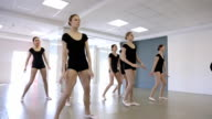 Handsome ballerinas jump with their trainer in classroom video