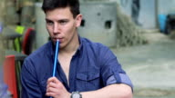 Handsome boy sitting, smoking hookah, girl coming to him and touching. Slowly video