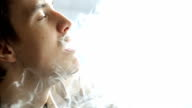 Handsome brunet smokes electronic hookah and enjoys view from windowsill video