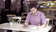 Handsome business owner doing the books using his tablet video