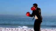 Handsome businessman boxing on the beach video