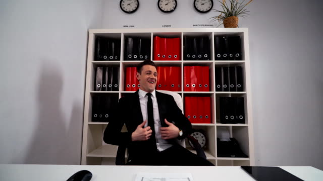 Handsome businessman funny dancing in office armchair video