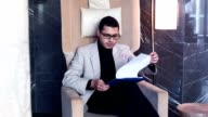 Handsome businessman in armchair checking up documents video