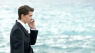 Handsome businessman in suit standing on the rocky shore and talking by phone. Sea waves on background video