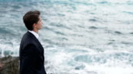 Handsome businessman in suit standing on the rocky shore and thoughtfully watches the sea waves on back view video