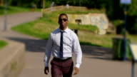 handsome businessman in the park: walking to the camera and smiling, portrait video