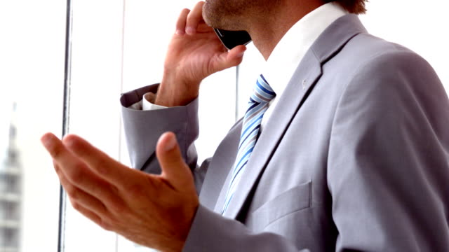 Handsome businessman looking out window talking on phone video
