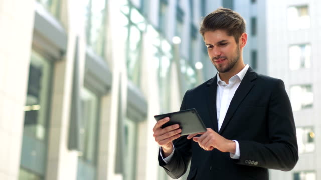 Handsome businessman read news on Tablet Computer, urban street public space video