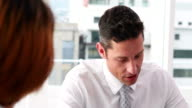 Handsome businessman talking with colleague at desk video