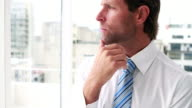 Handsome businessman thinking and looking out window video