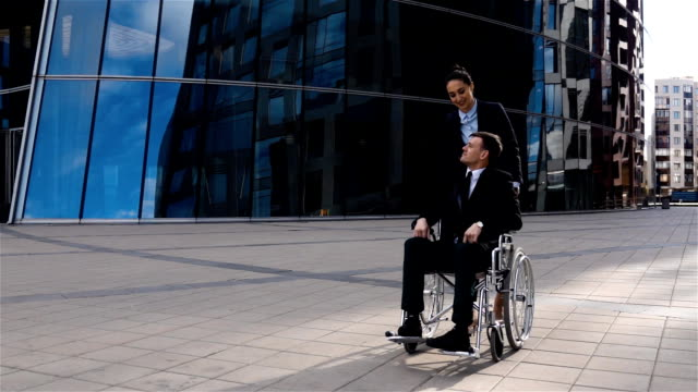 Handsome businesswoman cares for his colleague in wheelchair video