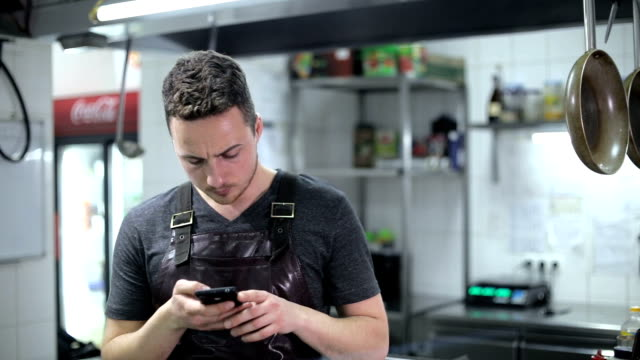 Handsome chef sending a text message in commercial kitchen video