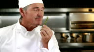 Handsome chef smelling rosemary and doing ok sign video