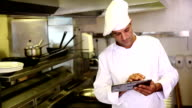 Handsome chef using tablet pc video