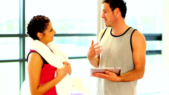 Handsome coach talking to sporty woman video