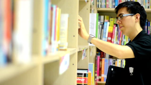 Handsome college student in library choose book video