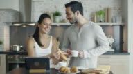 Handsome Couple in the Kitchen with Tablet on the Table. She eats Croissant He Drinks Coffee. video