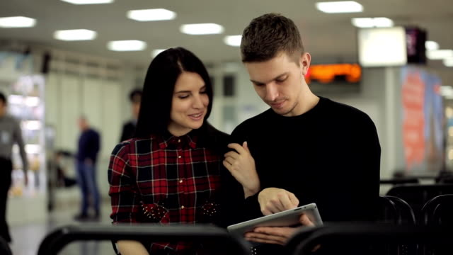 Handsome couple of people sits in departure lounge in airport video