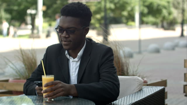 Handsome fashionable afro american business man stirring juice while usinh smartphone in outside cafe video