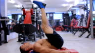 Handsome fit sporty man does abdominal exercises in the gym video