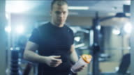 Handsome fit sporty man holds a shaker and poses in the gym. video
