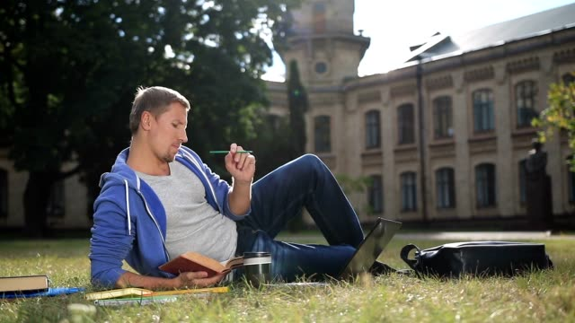 Handsome focused student studying on campus lawn video