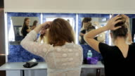 Handsome girls stand in front of mirror and create hairstyle video