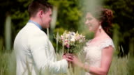 A handsome groom coming up to his beautiful bride in a wheat field, he gives her wedding bouquet, kisses her video